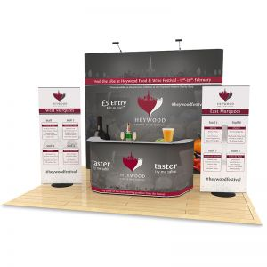 4m x 4m Jumbo Exhibition Stand Design includes a 2.9m High backdrop, 2 roller banners and double exhibition counter